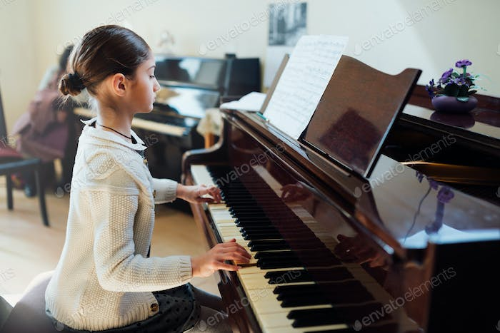 good student plays  piano at a music school