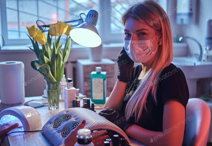 Master cosmetologist in mask and gloves sits at the manicure table and looks at the camera.