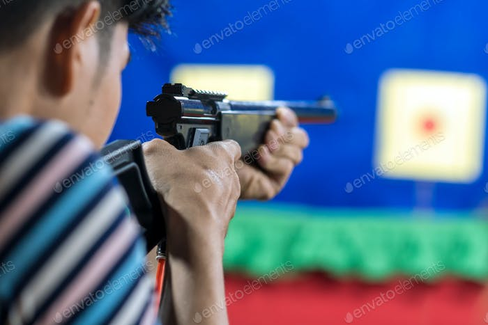 Rear view of man with his gun on shooting at the target in practice Shooting Range,