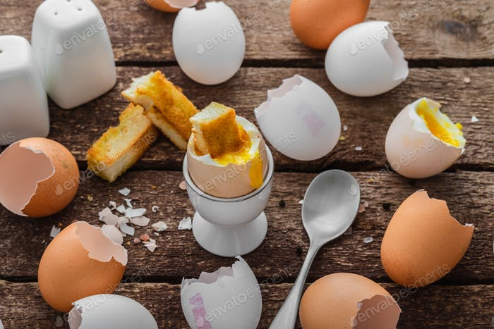Healthy breakfast with soft boiled egg and empty shells, rustic style