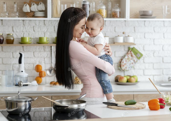 Young mom embracing with her baby son at kitchen
