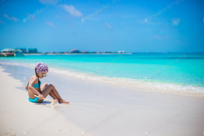 Little girl on seashore during summer vacation