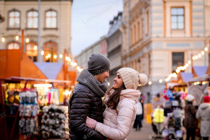 Romantic couple wearing winter clothes hugging while standing in evening street with Christmas fair