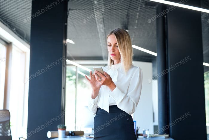 Businesswoman in her office with smartphone texting.