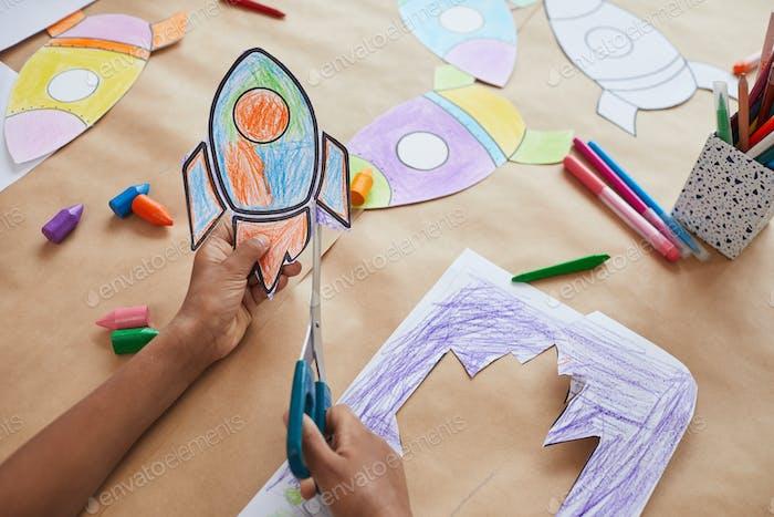 Unrecognizable Kid Cutting Paper Rockets