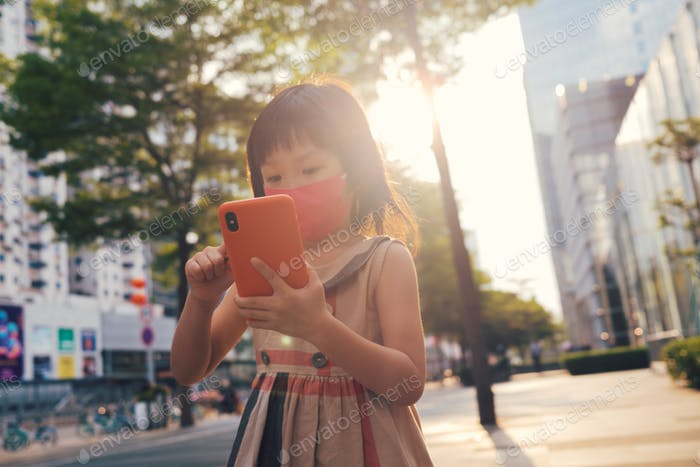 Asian child wearing mask and using cell phone in city