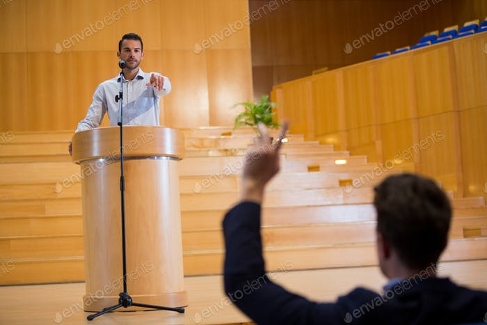 Business executive pointing towards audience