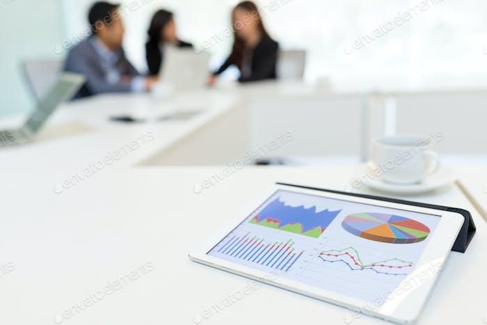 Цифровой планшет, отображающий диаграмму данных в конференц-зале