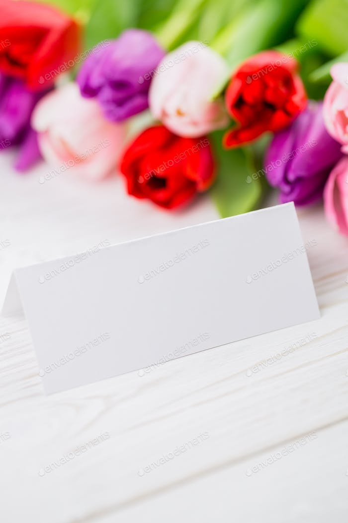 Colorful tulips and white card on wooden table