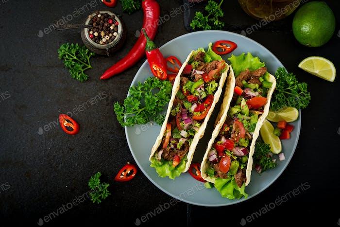 Mexikanische Tacos mit Rindfleisch in Tomatensauce und Salsa