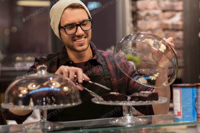 Mann oder Barmann mit Kuchen und Zange am Café-Tresen