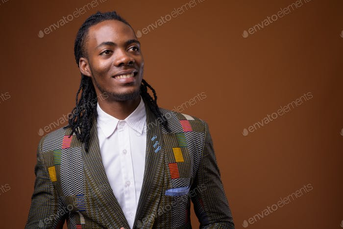 Young handsome African businessman against brown background