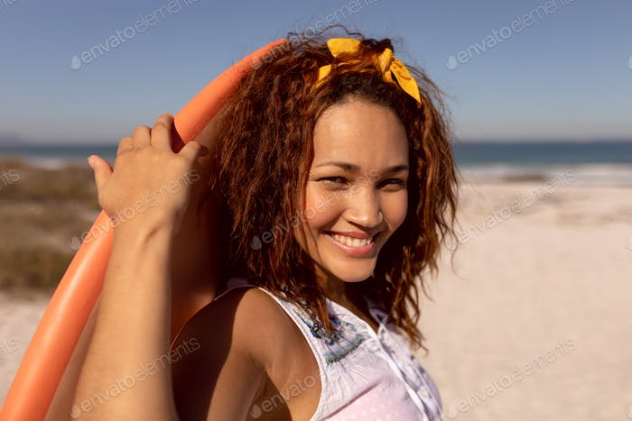 Beautiful happy Mixed-race woman with surfboard looking at camera on beach