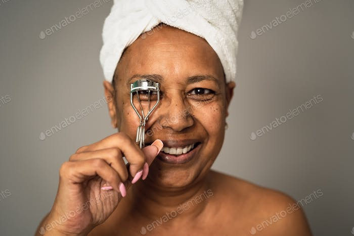 Happy African senior woman using eyelash curler - People beauty and wellness lifestyle concept