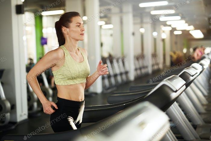 Sweaty Woman Running on Treadmill in Gym