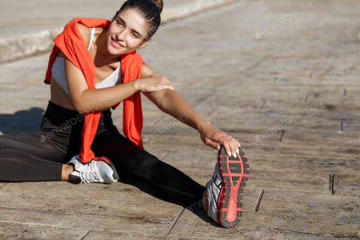 Close-up of attractive smiling sportswoman stretching leg and warming-up before training, exercising