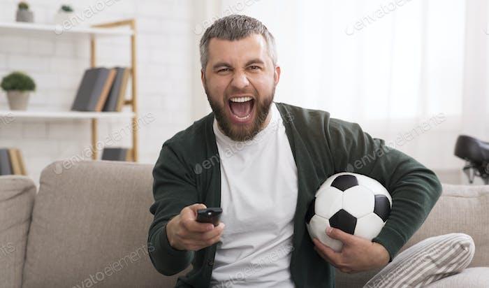Emotional man watching football game on TV