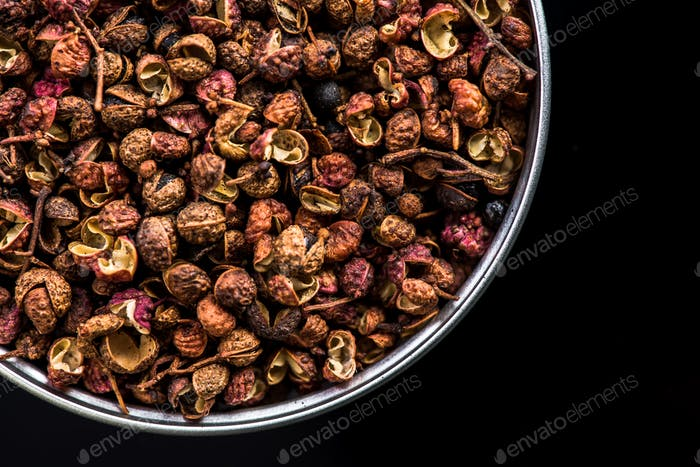 Sichuan pepper on pot on dark background