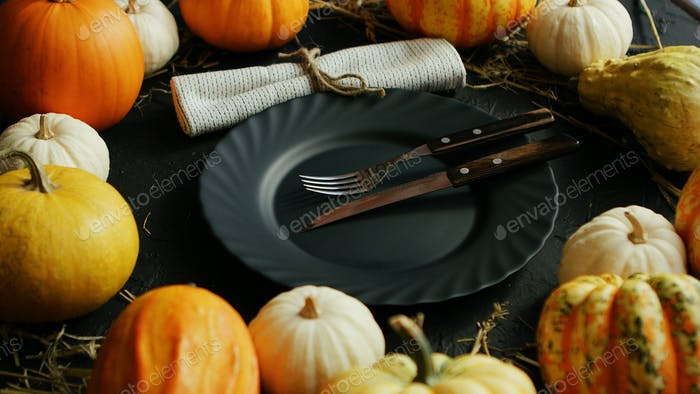 Black plate and cutlery surrounded by pumpkins