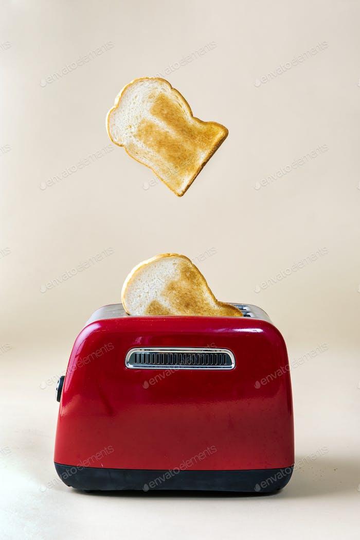 Geröstetes Toastbrot taucht von einem roten Toaster auf