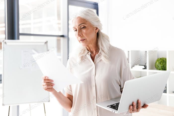 Confident mature business woman analyzing documents