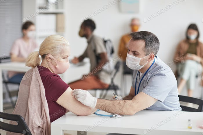 Doctor Vaccinating Senior Woman