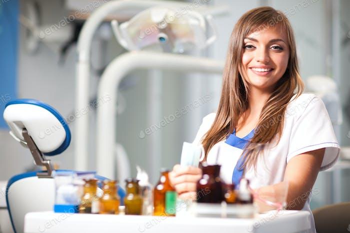 Junge Krankenschwester Frau in weißer Uniform sitzt in der Nähe von Zahnstuhl in der Zahnarztpraxis in der Klinik mit