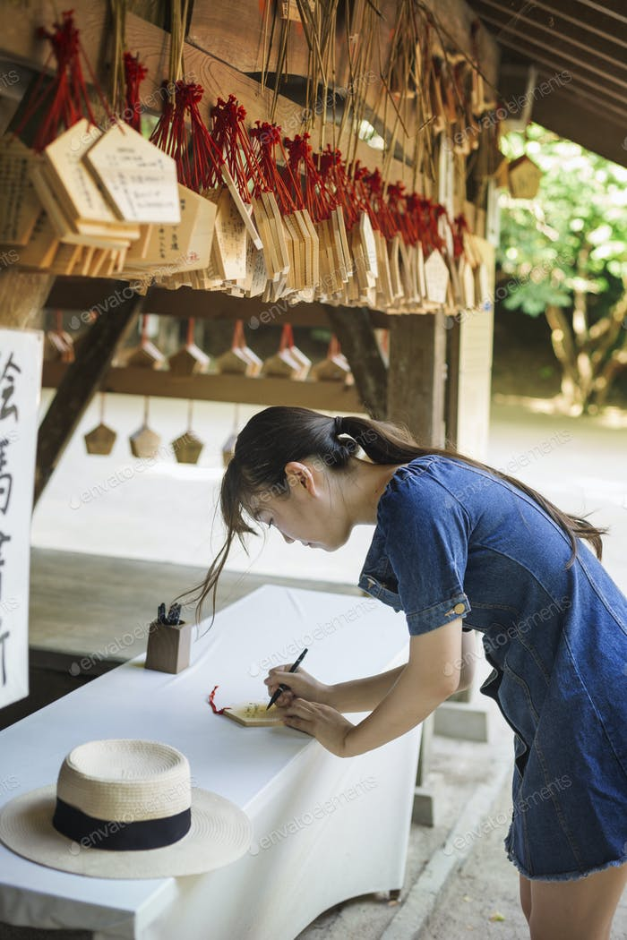 Young woman wearing blue dress writing on wooden fortune telling plaque at Shinto Sakurai Shrine,