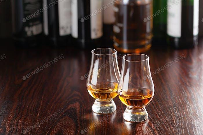 Bottles and glass of whisky spirit brandy on dark brown background