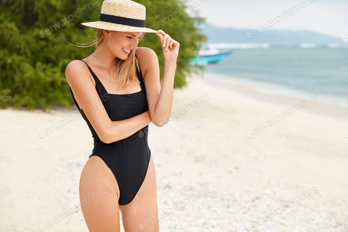 Young female adventurer in black bathing suit, has slender legs and perfect body shape, wears straw