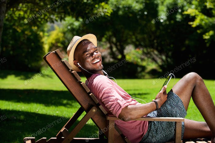 Happy young man relaxing on chair outdoors with digital tablet
