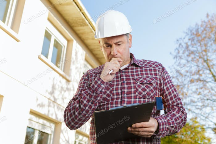 thoughtful worker builder in hardhat on the background of construction