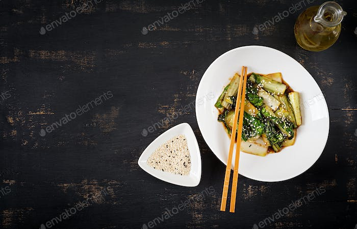 Bok choy vegetables stir fry with soy sauce and sesame seeds. Chinese cuisine. Top view