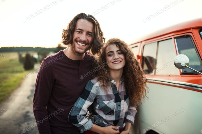A young couple on a roadtrip through countryside, standing by minivan.