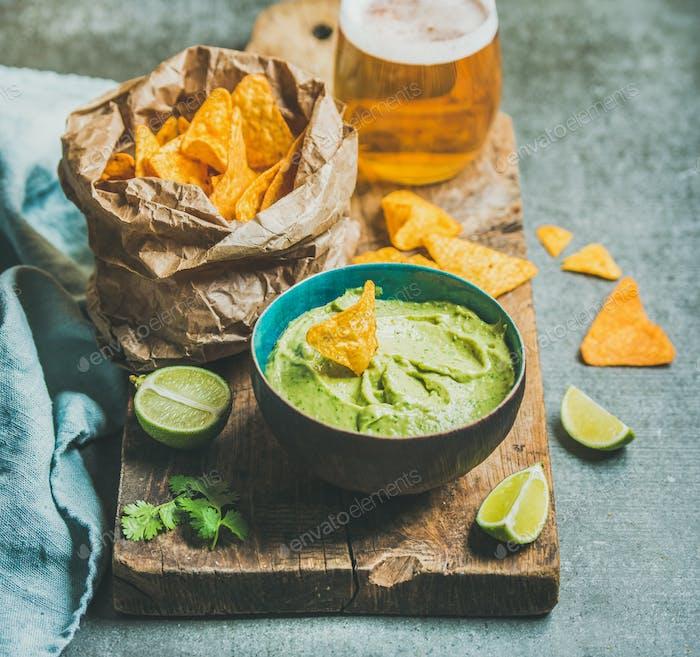 Fresh guacamole sauce in blue ceramic bowl, corn chips, beer