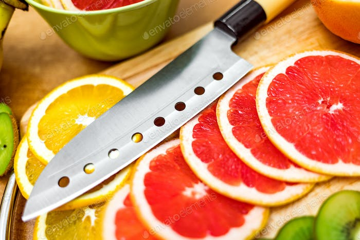 Sharp kitchen knife on cutting Board next to sliced grapefruit a