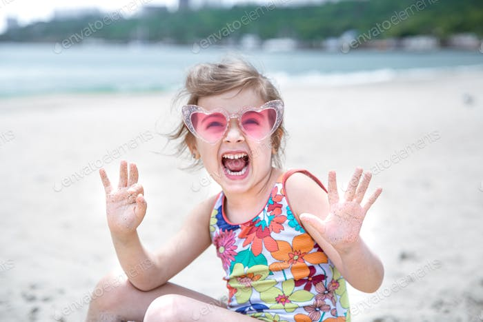 Ein kleines süßes Mädchen mit Brille spielt im Sand am Strand am Meer