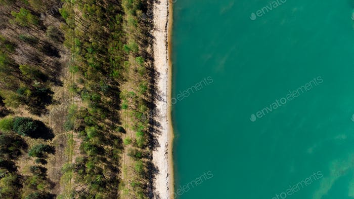 Aerial Drone View Top Down at Forest with Beach at Blue Lake Edge