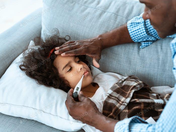 Coronavirus alert. African American girl having fever and worried grandpa nursing her at home