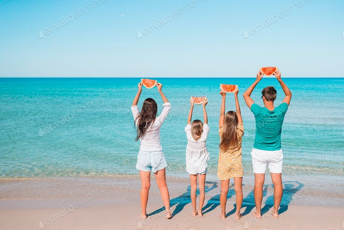 Happy family eating watermelon on the beach