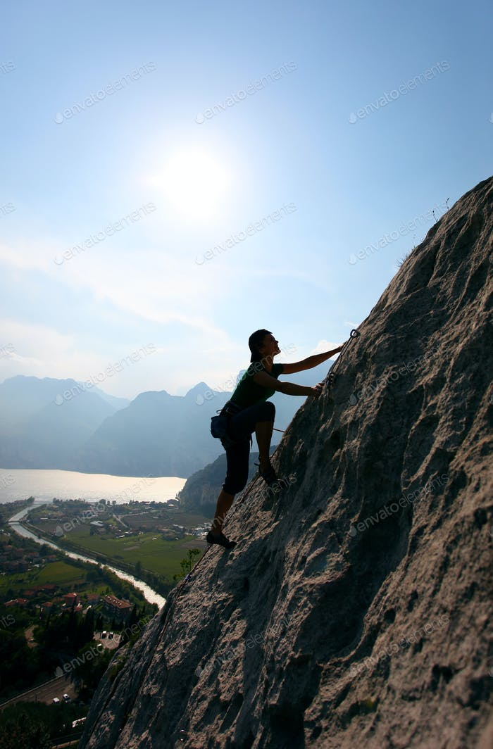 Silhouette of female climber against view of Lake Garda, Italy
