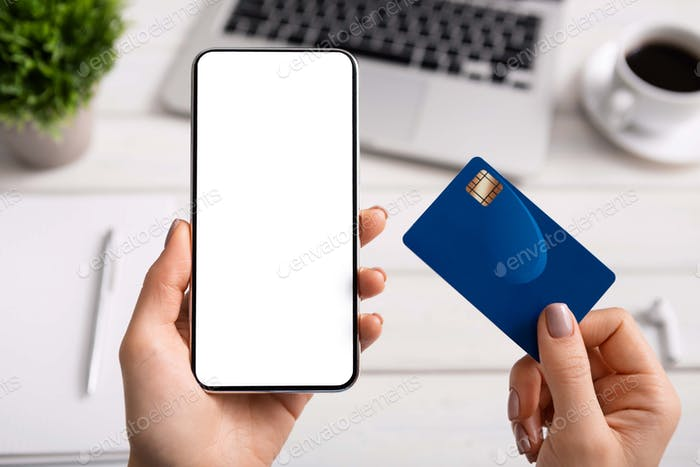 Woman using credit card and blank smartphone