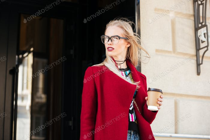 Amazing young caucasian woman walking outdoors drinking coffee.