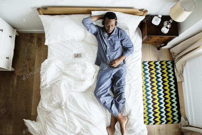 Man in bed listening to music