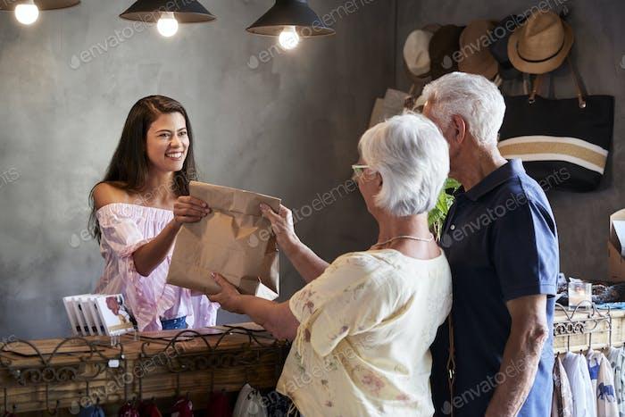 Ladenbesitzer, der hinter der Kasse steht und Senioren bedient