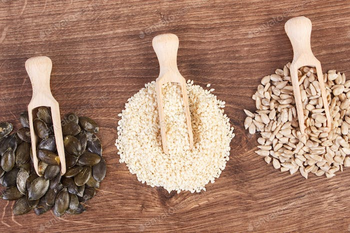 Sunflower, pumpkin and sesame seeds with wooden scoop on board, healthy nutrition concept