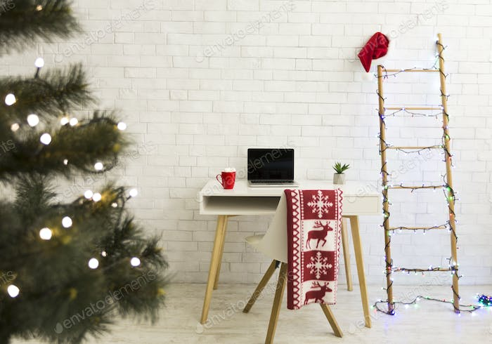 Cozy interior with Christmas decorations and laptop