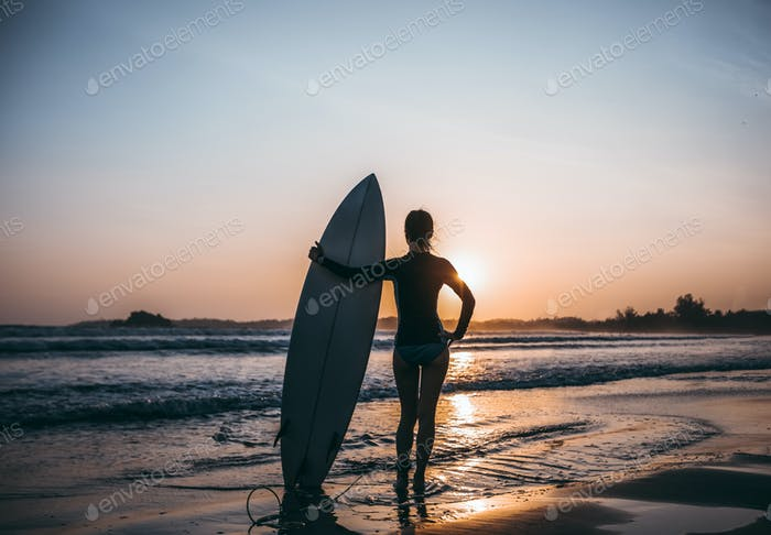 Surfer with surfboard on beach