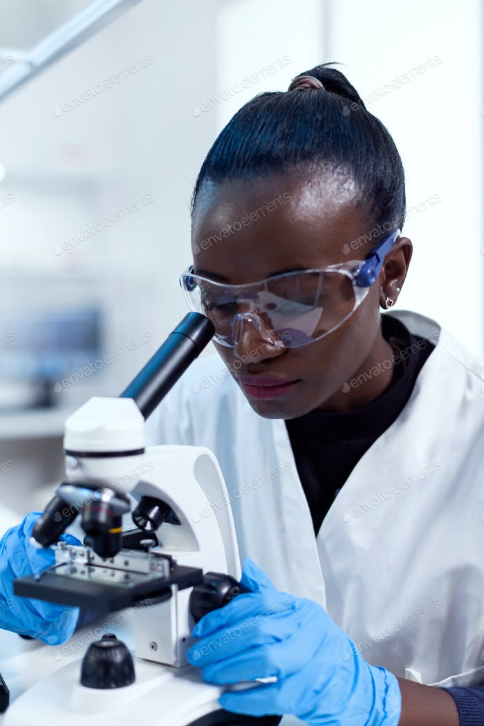 Biochemistry technician with african ethnicity using microscope