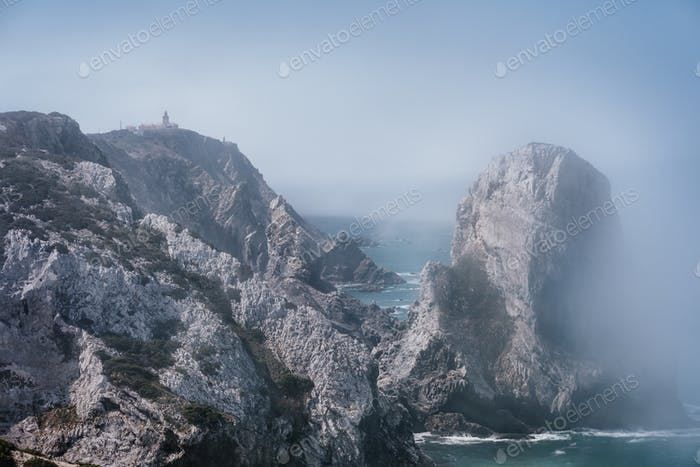 Rocky coastline of Praia Da Ursaa in morning fog, Sintra, Portugal. Giant sea stacks towering up